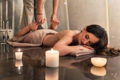 Ung kvinna som tycker om de sträckande teknikerna av den thailändska massagen arkivbilder