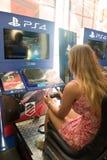 Ung kvinna som tycker om DriveClub, artikel med ensamrätt för PS4 Royaltyfria Bilder