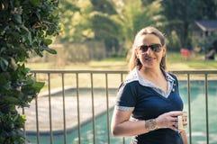 Ung kvinna som tycker om en kopp av tea i henne som är trädgårds- Fotografering för Bildbyråer