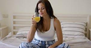 Ung kvinna som tycker om ett exponeringsglas av orange fruktsaft Royaltyfria Bilder
