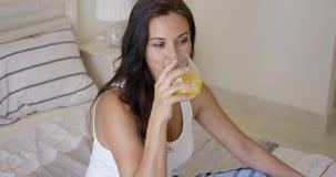 Ung kvinna som tycker om ett exponeringsglas av orange fruktsaft Royaltyfri Bild