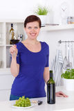 Ung kvinna som tycker om ett exponeringsglas av rött vin i henne kök Arkivfoton