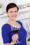 Ung kvinna som tycker om ett exponeringsglas av rött vin i henne kök Royaltyfria Foton