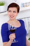 Ung kvinna som tycker om ett exponeringsglas av rött vin i henne kök Royaltyfria Bilder