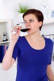 Ung kvinna som tycker om ett exponeringsglas av rött vin i henne kök Arkivbilder