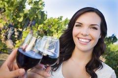 Ung kvinna som tycker om exponeringsglas av vin i vingård med vänner Royaltyfria Bilder