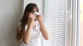 Ung kvinna som tycker om hennes morgonkaffe eller te och att stå, genom fönstret och att le Härlig romantisk oigenkännlig flicka lager videofilmer