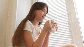 Ung kvinna som tycker om hennes morgonkaffe eller te och att stå, genom fönstret och att le Härlig romantisk oigenkännlig flicka stock video
