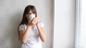 Ung kvinna som tycker om hennes morgonkaffe eller te och att stå, genom fönstret och att le Härlig romantisk oigenkännlig flicka arkivfilmer