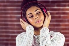 Ung kvinna som tycker om hennes musik Royaltyfri Foto
