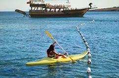Ung kvinna som tycker om hennes sommarsemester som kayaking i havet Fotografering för Bildbyråer