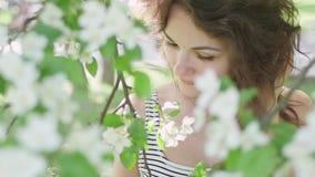 Ung kvinna som tycker om i bakgrunden av trädet arkivfilmer