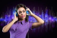 Ung kvinna som tycker om i musik Fotografering för Bildbyråer
