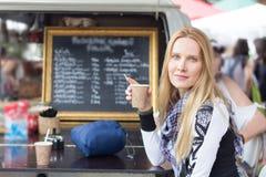 Ung kvinna som tycker om kaffe i utomhus- kafé arkivfoton