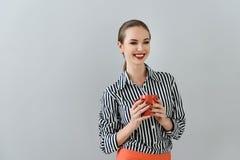 Ung kvinna som tycker om koppen kaffe i studio Arkivbild