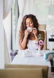 Ung kvinna som tycker om lukten av kaffe Arkivbild