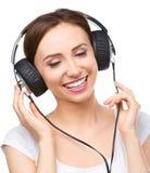 Ung kvinna som tycker om musik genom att använda hörlurar Royaltyfri Bild