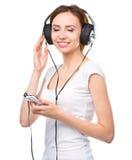 Ung kvinna som tycker om musik genom att använda hörlurar Royaltyfria Bilder