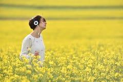 Ung kvinna som tycker om musik i hörlurar i naturen Arkivbild