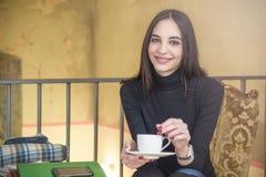 Ung kvinna som tycker om något kaffe i ett kafé royaltyfria bilder