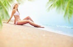 Ung kvinna som tycker om solig dag på den tropiska stranden arkivbild
