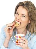 Ung kvinna som tycker om te och kex arkivbild