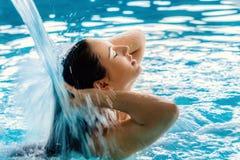 Ung kvinna som tycker om vattenkaskaden i brunnsort royaltyfria foton