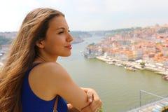 Ung kvinna som tycker om vind i hennes framsida, när se den Porto staden, Portugal, Europa arkivbilder