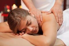 Ung kvinna som tycker om yrkesmässig massage arkivfoton