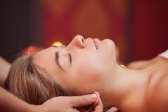 Ung kvinna som tycker om yrkesmässig massage royaltyfri foto