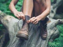 Ung kvinna som tyoing henne kängor i skog Arkivbild
