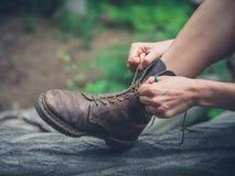 Ung kvinna som tyoing henne kängor i skog Royaltyfria Bilder