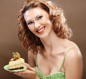 Ung kvinna som upp rymmer ett läckert stycke av caken royaltyfria bilder