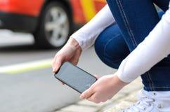 Ung kvinna som upp väljer hennes splittrade mobil Arkivbild