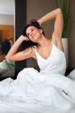 Ung kvinna som upp vaknar lyckligt och utvilat. Arkivfoton