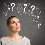 Ung kvinna som uppe i luften tänker med frågefläckar