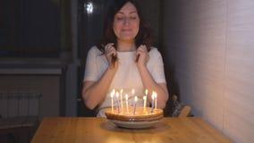 Ung kvinna som ut blåser stearinljus på feriekakan arkivfilmer