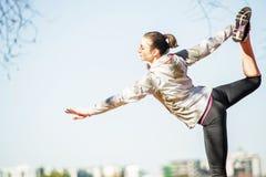 Ung kvinna som ut sträcker på bänk, innan att jogga Royaltyfri Fotografi