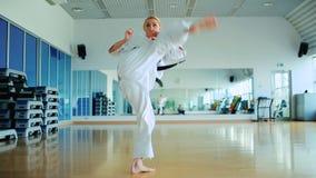 Ung kvinna som utbildar karatetricken i idrottshallen stock video