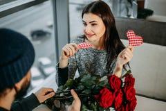 Ung kvinna som utbyter gåvor med hennes pojkvän på restaurangen V royaltyfri bild