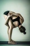 Ung kvinna som utför yogavridningen Arkivbilder