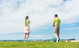 Ung kvinna som utomhus öva den korrekta flyttningen under golfgrupp Royaltyfria Bilder