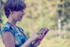 Ung kvinna som utomhus använder en rosa färgminnestavla Royaltyfri Fotografi