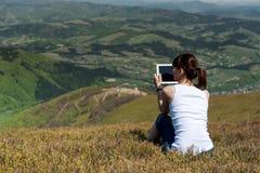 Ung kvinna som utomhus använder minnestavladatoren Arkivfoton