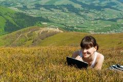Ung kvinna som utomhus använder minnestavladatoren Arkivbilder