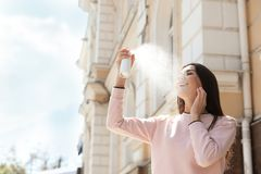 Ung kvinna som utomhus applicerar termiskt vatten på framsida kosmetisk produkt arkivbild