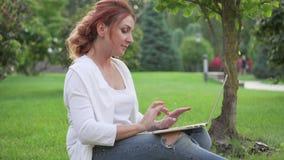 Ung kvinna som utomhus arbetar med bärbara datorn stock video