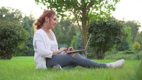 Ung kvinna som utomhus arbetar med bärbara datorn arkivfilmer