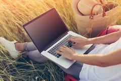Ung kvinna som utomhus arbetar med bärbara datorn i äng Arkivbild