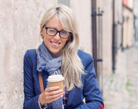 Ung kvinna som utomhus blinkar in i kameran, medan rymma en kopp kaffe Royaltyfria Bilder